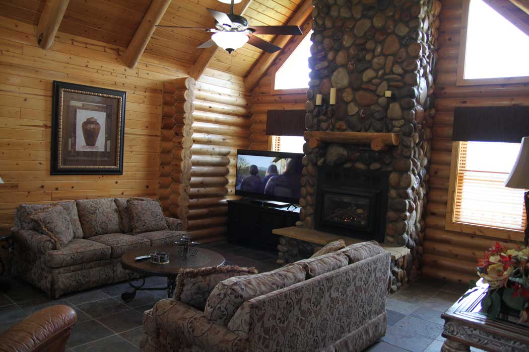 "Living room with fireplace and 65"" TV with satellite"